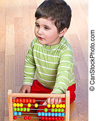 Caucasian baby in green shirt playing with bright colorful blocks