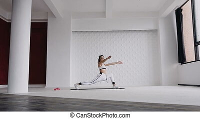 Caucasian beautiful blonde girl doing yoga asana on the floors in the gym near the big windows. Fitness training. Calmness and relax, woman happiness