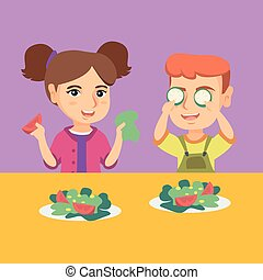 Caucasian boy and girl playing with vegetables.