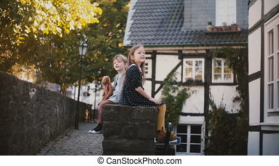 Caucasian boy and girl sit together, side view. Siblings on...