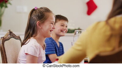 Caucasian boy and girl smiling while sitting on dining table. enjoying lunch together during christmas at home. christmas festivity celebration tradition