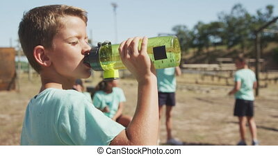 Caucasian boy drinking water at boot camp - Side view of a ...
