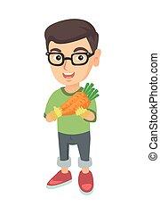 Caucasian boy in glasses holding fresh carrot.
