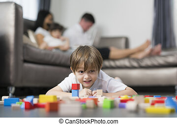 Caucasian boy play wooded toy in living room in home with his father and mother