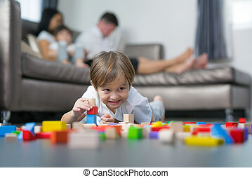Caucasian boy play wooded toy in living room