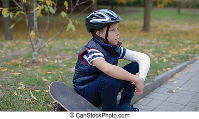 Caucasian boy sitting on the border with his skate