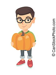 Caucasian boy standing with a big orange pumpkin.