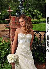 Caucasian bride leaning against a brick column - A 20...