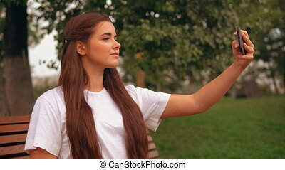 caucasian brunette use app on mobile outdoors - side view...