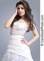 Caucasian Brunette Woman in White Dress Posing Against Gray Background.