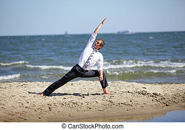 Caucasian business man practicing yoga on the beach