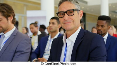 Front view of a Caucasian businessman attending a business seminar while smiling and looking at camera 4k