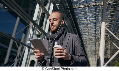 Caucasian businessman using business app on tablet computer, walking in city during a working lunch break. Handsome young businessman communicating on tablet, go confident, drinking coffee