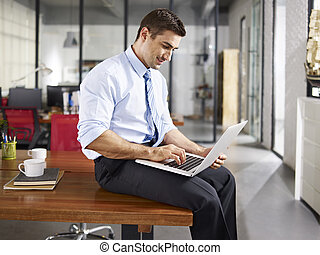 caucasian business executive sitting desk using laptop computer in office.