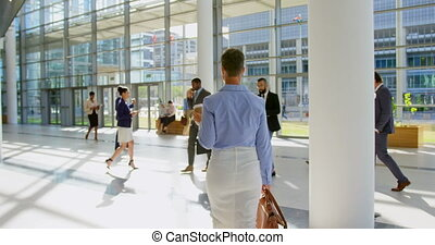 Caucasian businesswoman walking in the lobby at office 4k - ...