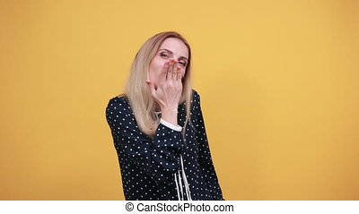 Caucasian charming young lady blowing, send air kiss over isolated orange background in blue shirt with white polka dot. Lifestyle concept