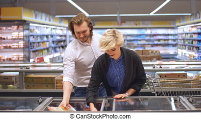 male and female shoppers push cart with grocery products in...