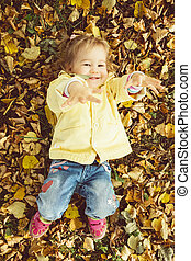 Caucasian child girl dressed in a jacket lies on the ground in autumn leaves