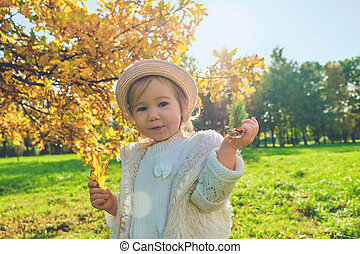 Caucasian child girl in rustic clothes walks with a hat in the park autumn