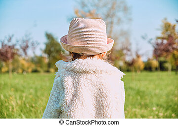 Caucasian child girl in rustic clothes walks with her back in the autumn park