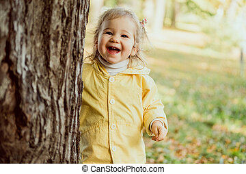 Caucasian child girl laughing walking in the park near a tree