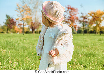 Caucasian child girl standing with her back in a hat in the park in autumn