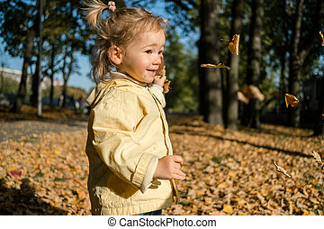 Caucasian child girl throws leaves in the park in autumn