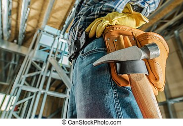 Caucasian Contractor Tools Belt Closeup with a Hammer. Construction Industry Theme