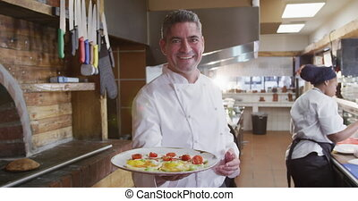 Caucasian cook showing his dish - Portrait of a happy ...