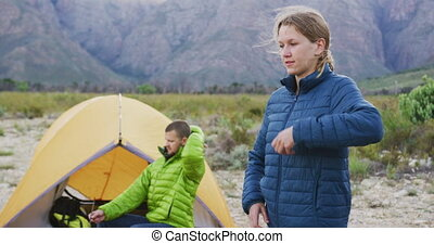 Caucasian couple having a good time on a trip to the mountains, camping in nature, wearing warm clothes, in slow motion