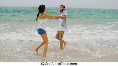 Caucasian couple having fun together on the beach 4k