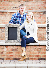 Caucasian couple sitting on brick steps