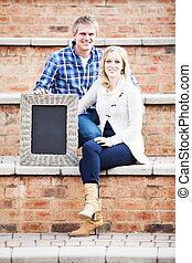 Caucasian couple sitting on brick steps