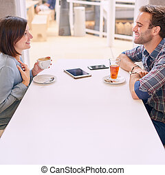 caucasian couple smiling at each other on date in cafe -...