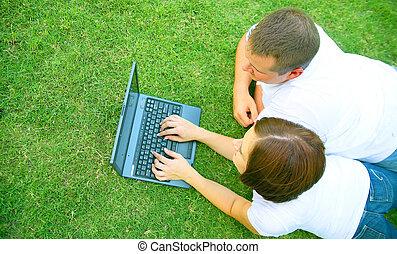 Caucasian Couple Using Laptop Outdoor