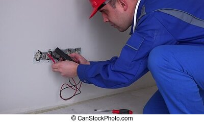 Caucasian electrician working on wall socket. Static closeup...