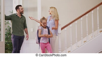 Caucasian couple and their daughter entering the front door of their house, embracing, the girl wearing backpack dancing in hall, in slow motion.
