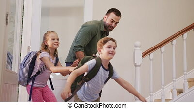 Caucasian couple, their son and daughter entering the front door of their house, the children wearing backpack and running ahead, in slow motion.