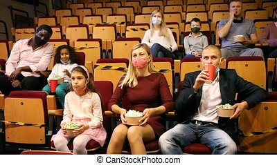 caucasian family in mask sitting at premiere in cinema mother, father and their children sitting at film in auditorium during epidemic. High quality FullHD footage