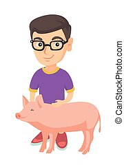 Caucasian farmer boy in glasses stroking a pig.