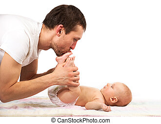 Caucasian father kissing feet of his baby son
