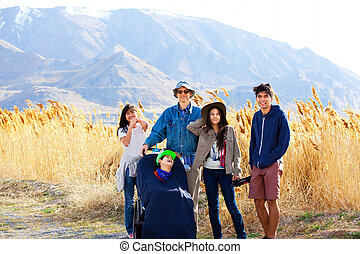 Caucasian father standing by field of tall grasses with biracial children. Youngest in wheelchair.