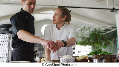 Caucasian female and male chefs making dough in a bowl. preparing dishes and smiling. at work in a professional kitchen.