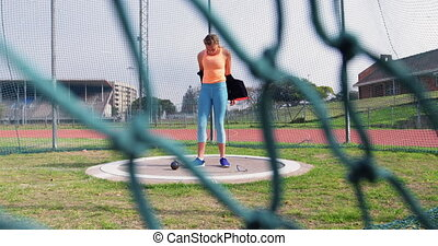 Caucasian female athlete getting ready for shot put game at sports venue. She is standing at sports venue 4k