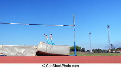 Caucasian female athlete practicing high jump at sports venue. Blue sky in the background 4k