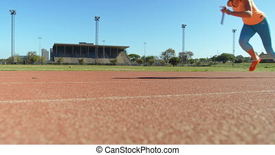 Caucasian female athlete running race on race track at sports venue. She is fit and healthy 4k