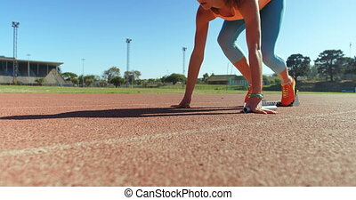 Caucasian female athlete taking starting position and ...