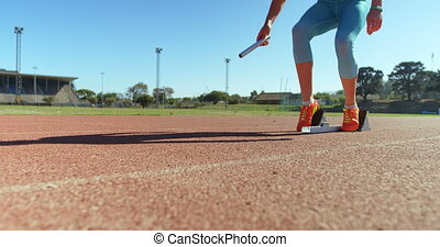 Caucasian female athlete taking starting position on a running track at sports venue. She is ready for a race 4k