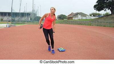 Caucasian female athlete walking with discus throw at sports venue. She is getting ready for a discus throw 4k