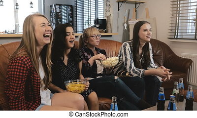 Caucasian female friends watch popular TV show. Happy...